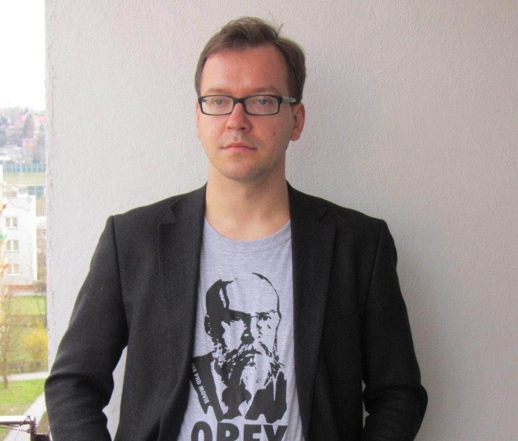 Zdjęcie przedstawia sylwetkę prof. dr hab. inż. Piotra Faliszewskiego na tle białej ściany.